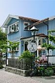 Blick auf restauriertes Landhaus- Café mit hellblauer Holzfassade, idyllischem Vorgarten und lauschigem Terrassenplatz