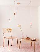 Coffeetable in hellem Holz, auf zartrosa Teppichmuster, ergänzt durch den weichem Kupferschimmer von Stuhl und Hängelampen