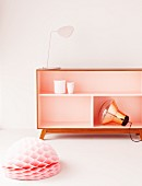 Pendant lamp with copper shade, pink table lamp, pink sideboard with champagne-coloured interior and honeycomb paper ball