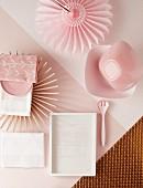 Kleine Tischdeko mit strahlenförmigem Set, Papierfaltblüte und Schalen in gehauchten Rosa- und Champagnertönen