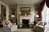 Wide armchairs in front of English fireplace with ornaments on mantelpiece and fender seat