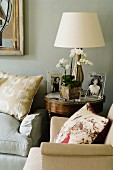 Photos, orchid and lamp with lamps shade on side table between two armchairs