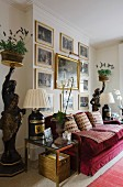 Gilt-framed, historical paintings above red velvet sofa flanked by antique tray supports with pots of lavender