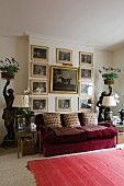Gilt-framed, historical paintings above red velvet sofa flanked by side tables and statues holding plants on trays