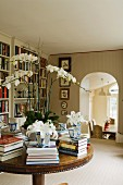 Stacked books arranged in circle and white orchid on antique table in library