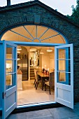 Open double glass doors and segmented transom window in brick facade; view into kitchen-dining room in romantic candlelight