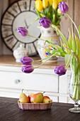 Lila und gelbe Tulpen, sowie eine Schale Birnen in der Küche