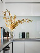 Detail of fitted kitchen - glass vase of flowering branches on stainless steel worksurface, wall units and base units with white doors