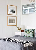 Black and white geometric blanket and grey bed linen on bed below glass louvre window in corner