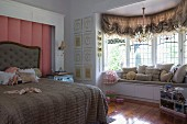 Modern window seat with storage drawers in window bay in dramatic, antique-style girl's bedroom in historical house