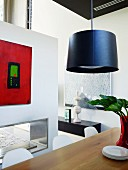 Pendant lamp above dining table and modern painting on partition wall