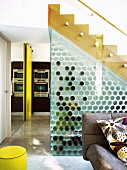 Storage space below stairs behind glass wall with honeycomb wine rack