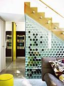 Storage space below stairs behind glass wall with honeycomb wine rack