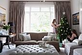 Two girls decorating Christmas tree in elegant living room