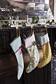 Christmas stocking hung from motto ornaments with hook on marble mantelpiece