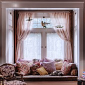 Cat lying on window seat with many scatter cushions and romantic curtains