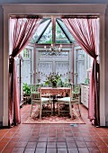 Romantic conservatory with dining table, rug and curtains