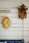 Straw hat next to cuckoo clock on white wooden wall
