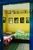 View into bedroom with twin beds, yellow-painted walls and framed religious pictures