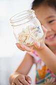 Little girl holding glass jar of starfish and seashells