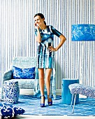 Accessories, wallpaper and rug with blue print pattern in trendy seating area: woman speaking on phone wearing matching clothes