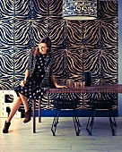 Dining area with wire mesh chairs in front of elegant, zebra-patterned wallpaper and woman wearing polka-dot dress