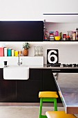 Fitted kitchen with black units, stainless steel worksurfaces, colourful accents and shelf above sink