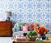 Sofakissen mit buntem Mustermix auf Sofa vor blau-weisser Tapete mit Kreismuster