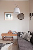 Designer ceiling lamp in corner above grey sofa and vintage suitcase below side table