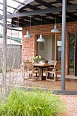 Industrial lamps above dining area on roofed terrace of Australian, 1920s house with brick facade