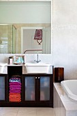 Bathroom with brightly coloured towels in washstand base unit