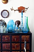 Antlers on wall above colourful glassware on vintage apothecary's cabinet