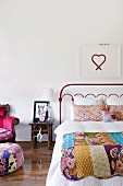 Picture of heart above red metal bed with patchwork blanket