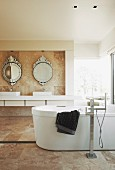 Free-standing bathtub in marble-tiled bathroom; washstand below round, ornate, antique-style mirrors