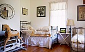 Metal beds, wooden rocking horse on old iron mechanism and collection of pictures in vintage bedroom