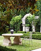 Metal chair at classic stone table in garden; antique columns, arches and urns behind low box hedge