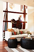 Pale sofa and black, wicker side tables; horse saddle on wooden, frame-like partition and surfboards in background