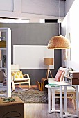 Seating area in youthful Scandinavian style with wicker lampshade and partition shelving
