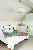 Double bed next to wardrobe in white, modern bedroom with sloping attic ceiling