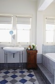 Bathroom with vintage washstand, diagonal chequered floor and bathtub on platform