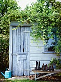 Garden shed with rustic wooden door and shoes on weathered wooden bench
