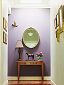 Horse figurine and table lamp on antique console table and mirror on lilac-painted wall in hallway