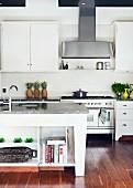 Küchenblock mit Spüle und teilweise offenem Regal vor Einbauküche im Landhausstil