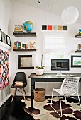 Office area with dark wooden table, metal chair, shell chair, floating shelves & cowhide rug