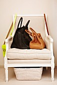 Ladies' leather handbags on white, antique armchair with wicker basket underneath