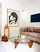 Classic coffee table on flokati rug and leather couch in corner; portrait of woman on wall
