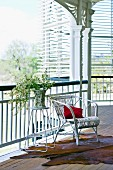 Vase of flowers on side table next to white rattan chair on veranda