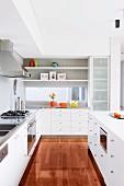 Moderne Einbauküche mit weissen Fronten und hochglänzendem Parkettboden