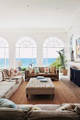 Pale sofa set and ottoman in Mediterranean living room with sea view through arched French windows
