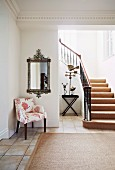 Open-plan stairwell in elegant villa with upholstered chair and mirror on wall